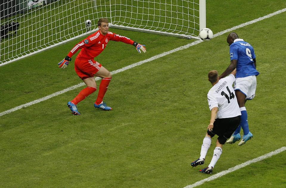 Italy's Mario Balotelli scores the opening goal past Germany goalkeeper Manuel Neuer, left, during the Euro 2012 soccer championship semifinal match between Germany and Italy in Warsaw, Poland, Thursday, June 28, 2012. (AP Photo/Vadim Ghirda)