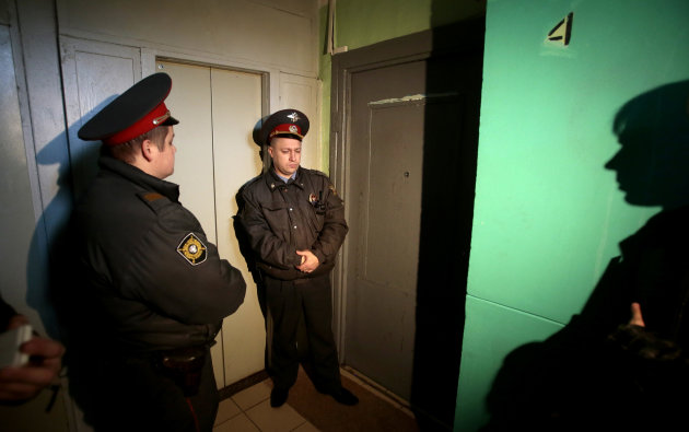 Police officers guard the lobby of an apartment where Russia opposition leader Sergei Udaltsov lives, Moscow, Wednesday, Oct. 17, 2012. In a new sign of a widening crackdown on Russian opposition, investigators on Wednesday opened a criminal probe against leftist leader Sergei Udaltsov and several other opposition activists for their alleged role in plotting mass riots. (AP Photo/Mikhail Metzel)
