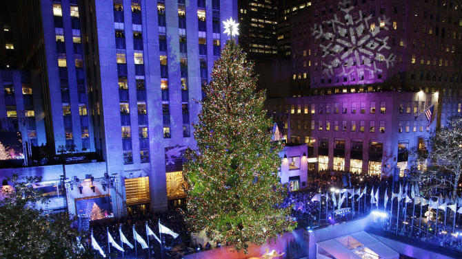 In this Wednesday, Nov. 28, 2012 photo, the Rockefeller Center Christmas tree is lit during the 80th annual tree lighting ceremony at Rockefeller Center in New York. Scientists are working to decipher the DNA code of conifers, like this Norway spruce at Rockefeller Center in New York. In late 2012, scientific teams in the United States and Canada have released preliminary, patchy descriptions of conifer genomes. And a Swedish team plans to follow suit soon in its quest for the Norway spruce. (AP Photo/Kathy Willens)