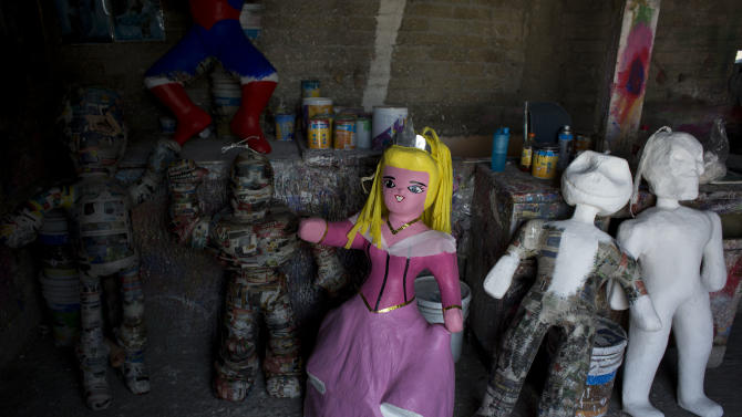 """In this Jan. 20, 2015 photo, a piñata resembling Sleeping Beauty stands among other partially finished piñatas, inside the workshop of Melesio Vicente Flores and his wife Cecilia Albarran Gonzalez, in the Iztapalapa neighborhood of Mexico City. Piñata vendors keep the craftsmen apprised of the market. Perennial favorites among the different figures include Spiderman, Mickey Mouse and Buzz Lightyear. Characters from the Disney hit """"Frozen"""" currently appear to be top sellers in local markets, while Albarran says """"princesses never go out of fashion."""" (AP Photo/Rebecca Blackwell)"""
