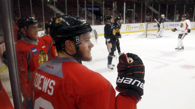 Chicago Blackhawks right wing Marian Hossa, left, and center Jonathan Toews wait along the boards during NHL hockey practice, Tuesday, June 11, 2013 in Chicago. The Blackhawks host the Boston Bruins in Game 1 of the Stanley Cup finals on Wednesday. (AP Photo/Charles Rex Arbogast)