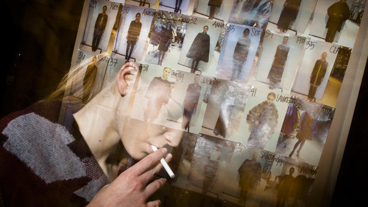 In this photo made with multiple flash exposures, a model smokes an electronic cigarette backstage before the Chado Ralph Rucci Fall 2013 collection is shown during Fashion Week, Sunday, Feb. 10, 2013, in New York. (AP Photo/John Minchillo)