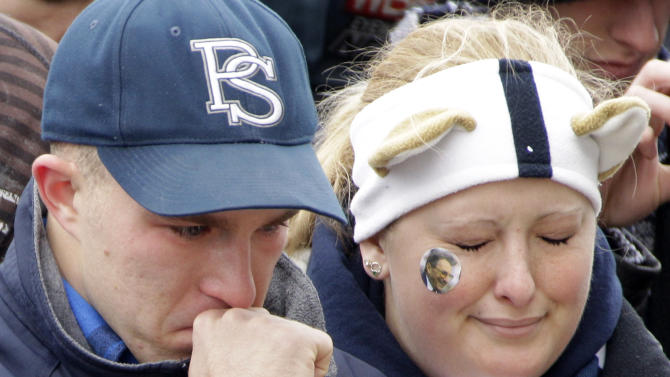 Molly Johnson, right, a Penn State student from Wilmington, Del., and fellow student, senior Ian Kenney pay their respects at a statue of Joe Paterno outside Beaver Stadium on the Penn State University campus after learning of Paterno's death on Sunday, Jan. 22, 2012, in State College,Pa. (AP Photo/Gene J. Puskar)