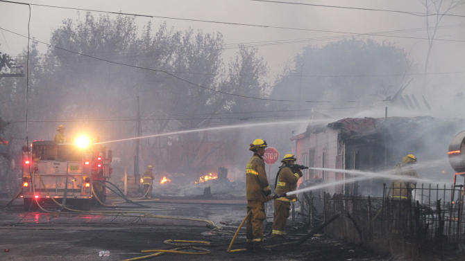Firefighters work to put out fires and protect structures along Center Street Monday, Sept. 15, 2014, in Weed, Calif. The, fire driven by fierce winds, raced through a small town near the Oregon border on Monday, burning a church to the ground, damaging or destroying 100 homes and prompting evacuation orders for at least 1,500 people, authorities said.(AP Photo/The Record Searchlight, Greg Barnette)