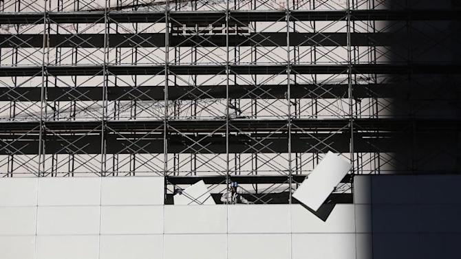 Workers carry building material at a construction site as they rebuild a hospital in Tokyo