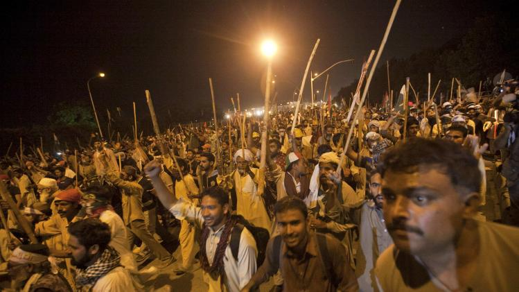 Supporters of Tahir ul-Qadri carry sticks while marching to the Prime Minister's house during the Revolution March in Islamabad
