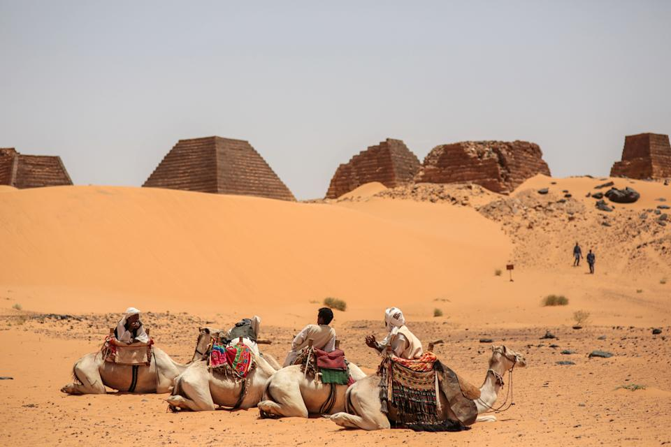 In this Thursday, April 16, 2015 photo, tour guides wait for tourists to offer them camel rides at the historic Meroe pyramids in al-Bagrawiya, 200...