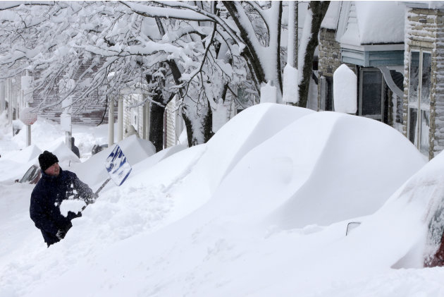 A man shovels snow off his car in front of his home on East Third street in the South Boston neighborhood in Boston, Saturday, Feb. 9, 2013.  A howling storm across the Northeast left the New York-to-