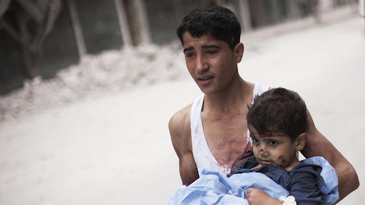 In this Thursday, Oct. 11, 2012 photo, a Syrian youth holds a child wounded by Syrian Army shelling near Dar al-Shifa hospital in Aleppo, Syria. (AP Photo/ Manu Brabo)