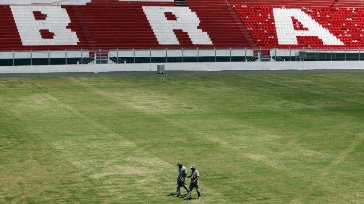 Workers walk along the field of Ponte Preta soccer club's Moises Lucarelli stadium, where Portugal's national soccer team will be training during the 2014 World Cup in Campinas