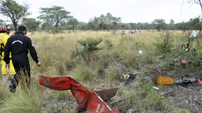 Rescue workers inspect the site where the former Paraguayan presidential candidate Lino Cesar Oviedo died after a helicopter crash in Chaco region, some 60 miles north of Asuncion, Paraguay, Sunday, Feb. 3, 2013. Oviedo was returning with his bodyguard from a political rally in northern Paraguay Saturday night when his pilot encountered bad weather. All three were killed in the crash, said Johnny Villalba, a spokesman for Paraguay's airport authority. (AP Photo/ABC, Roque Gonzalez)
