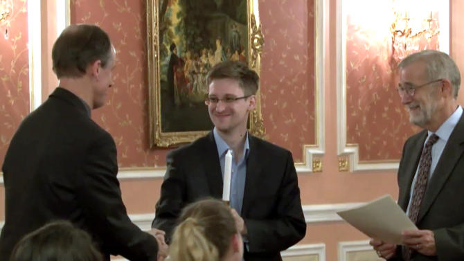 FILE - In this image made from video released by WikiLeaks on Oct. 11, 2013, former National Security Agency systems analyst Edward Snowden, center, receives the Sam Adams Award in Moscow, Russia. Europe bristles following Snowden's latest revelations about NSA tactics, including the alleged tapping of up to 35 world leaders' cell phones, which threaten to undermine America's ability to put its imprint on world affairs. At right is Raymond McGovern, a former U.S. government official, at left is former NSA executive Thomas Drake. (AP Photo, File)