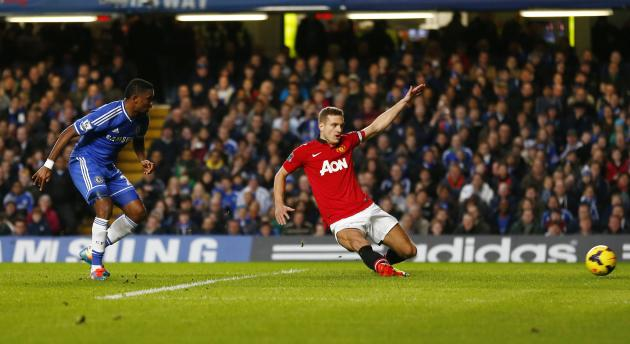 Chelsea's Eto'o shoots past Manchester United's Vidic to score during their English Premier League soccer match at Stamford Bridge