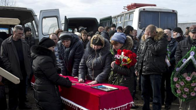 Relatives of a worker Prisyazhnyi, killed by a blast at Zasyadko coal mine, mourn next to coffin during funeral ceremony in Donetsk