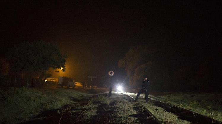 Federal police secure an area of the railroad tracks as they prepare to stop and raid a northbound freight train in search of Central American migrants, in San Ramon, Mexico, just after midnight on Friday, Aug. 29, 2014. The largest crackdown by Mexican authorities on illegal migration in decades has decreased the flow of Central American migrants trying to reach the United States, and has dramatically cut the number of child migrants and families, according to officials and eyewitness accounts along the perilous route. (AP Photo/Rebecca Blackwell)
