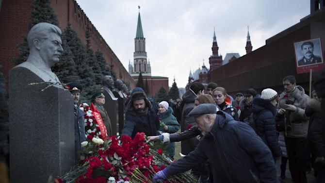 Russian communists put flowers at the Monument at Joseph Stalin's grave at the Kremlin wall at the Moscow's Red Square marking the 135th anniversary of the birth of Soviet dictator Josef Stalin in Moscow, Russia, Sunday, Dec. 21, 2014. (AP Photo/Alexander Zemlianichenko)