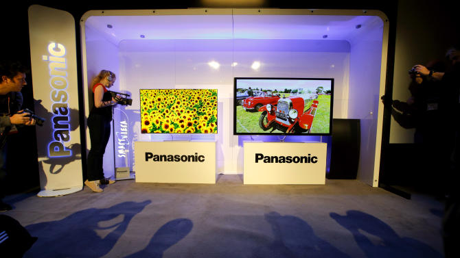 Show attendees photograph Panasonic's new televisions during a news conference at the International Consumer Electronics Show in Las Vegas, Monday, Jan. 7, 2013. The 2013 International CES gadget show, the biggest trade show in the Americas, is taking place in Las Vegas this week. (AP Photo/Jae C. Hong)