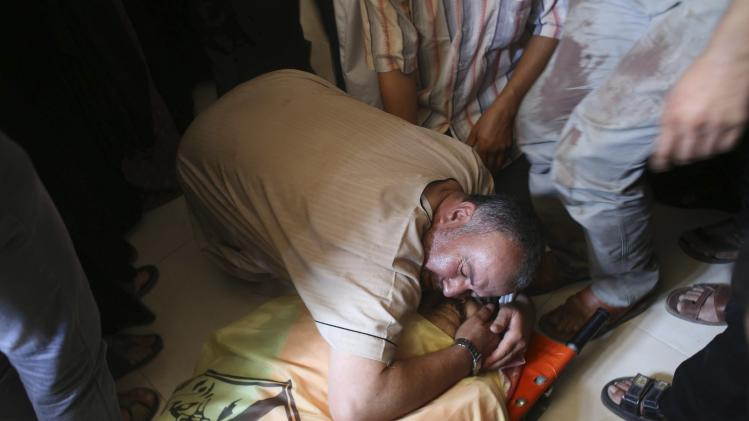 A Palestinian relative of Tawfiq al -Aga, who medics said was killed in Israeli shelling, mourns over his body during his funeral in Khan Younis in the southern Gaza Strip