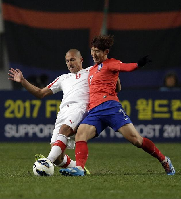 Switzerland's Gokhan Inler, left, fights for the ball against South Korea's Son Heung-min during their friendly soccer match at Seoul World Cup Stadium in Seoul, South Korea, Friday, Nov. 15, 2013. So