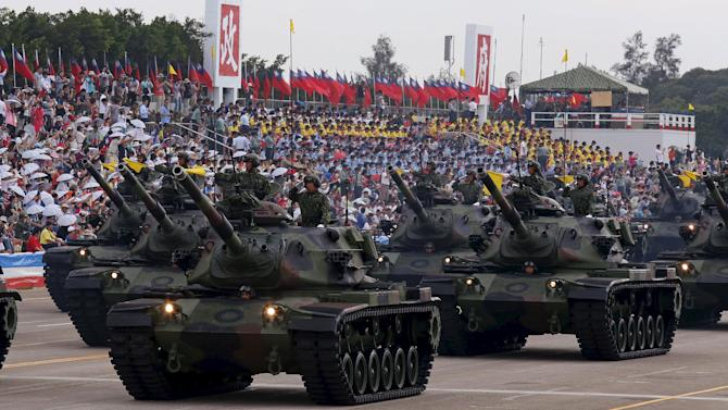 Military personnel salute as they stand on M60A3 main battle tanks displayed during the annual Han Kuang military exercise in an army base in Hsinchu