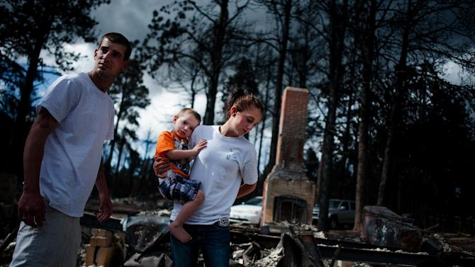 Ritchie Lewis, Brandy Burton and their son Caiyleb Lewis, 2, help sift through the rubble of their family's home that was completely destroyed in the Black Forest Fire, Tuesday, June 18, 2013, in Colorado Springs, Colo. Residents were allowed back into the area for a short period of time to view the properties that sustained the most damage from the fire. The Black Forest Fire, the most destructive wildfire in Colorado history, has destroyed 502 homes and charred more than 22 square miles. It was 85 percent contained Tuesday. (AP Photo/The Colorado Springs Gazette, Michael Ciaglo) MAGS OUT