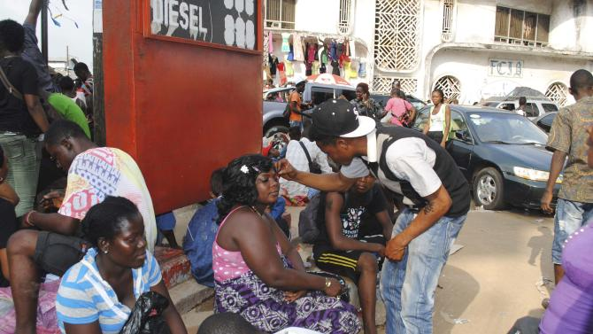 A woman has makeup applied on street during Christmas Eve celebrations in Monrovia