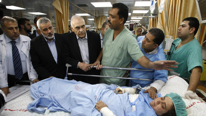 Egypt's Foreign Minister Mohamed Kamel Amr, third left, and Hamas Prime Minister in Gaza Ismail Haniyeh, second left, look at a Palestinian woman, who Palestinian medics claim was wounded in an Israeli air strike, at a hospital in Gaza City, Tuesday, Nov. 20, 2012. (AP Photo/Ahmed Zakot, Pool)