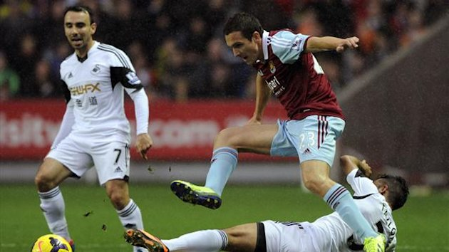 Swansea City's Neil Taylor (R) challenges West Ham United's Stewart Downing with Swansea City's Leon Britton (L) during their English Premier League match (Reuters)