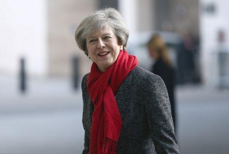 UK PM May promises frank talk with Trump after women protest