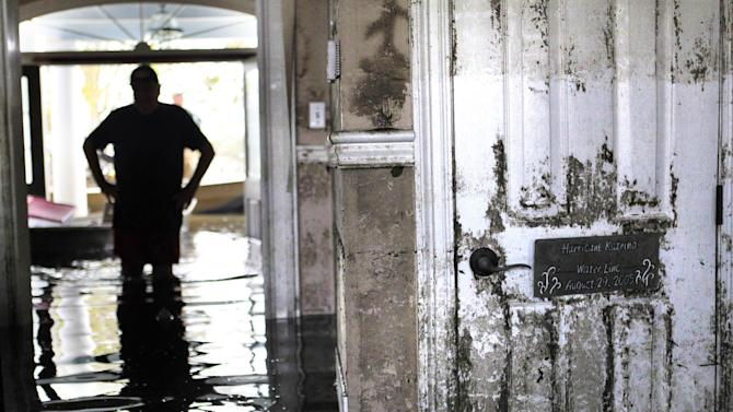 Don Duplantier walks through his flooded home as water recedes from Hurricane Isaac in Braithwaite, La., Sunday, Sept. 2, 2012. In the foreground is a sign marking the waterline from Hurricane Katrina, but floodwater from Isaac went all the way up to the second floor. (AP Photo/Gerald Herbert)