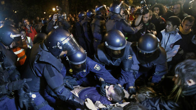 Police clash with protestors during a demonstration at the parliament against austerity measures announced by the Spanish government in Madrid, Spain, Wednesday, Sept. 26, 2012. Spain's Parliament has taken on the appearance of a heavily guarded fortress with dozens of police blocking access from every possible angle, hours ahead of a protest against the conservative government's handling of the economic crisis. (AP Photo/Andres Kudacki)