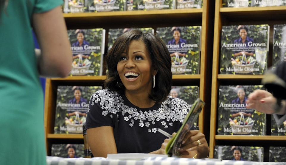 "First lady Michelle Obama signs copies of her book ""American Grown: The Story of the White House Kitchen Garden and Garden Across America"" at the Politics & Prose bookstore in Washington, Tuesday, May 7, 2013. (AP Photo/Susan Walsh)"