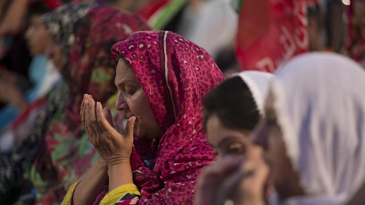 Supporters of Pakistani cricket celebrity-turned-politician Imran Khan pray for their leader's success during an anti-government sit-in protest in Islamabad, Pakistan, Friday, Aug. 29, 2014. Pakistan's prime minister on Friday denied asking the country's military chief to mediate with opposition leaders and protesters who have camped for two weeks outside parliament in the capital, Islamabad, demanding his resignation over alleged voting fraud. (AP Photo/B.K. Bangash)