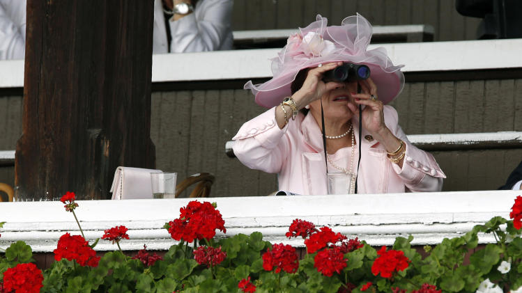 FILE - In this July 20, 2012 file photo, a woman watches the fifth horse race on opening day at Saratoga Race Course in Saratoga Springs, N.Y. Saratoga Springs' racetrack is still going strong as it marks its 150th anniversary this summer, the centerpiece attraction in a town that's also known for mineral springs, Victorian charm and upscale hotels, shops and restaurants. (AP Photo/Mike Groll, File)