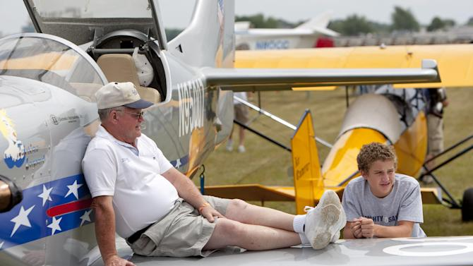 FILE - In this July 27, 2009, file photo, Lanny Rundell of Winnsboro, La. and his grandson Cole Uffman take a rest on their plane at the Experimental Aircraft Association's AirVenture in Oshkosh, Wis. One of the nation's largest air shows begins Monday, July 29, 2013, in Wisconsin, and for each of the 10,000 planes flying in, the federal government will collect about $45 for air traffic control services. The fee has angered pilots, who already pay for air traffic control through a fuel tax. (AP Photo/Mike Roemer, File)