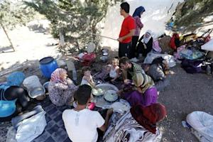 Syrian refugees eat and rest by the roadside in Kilis