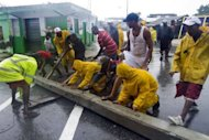 Local residents move a piller after the passage of Tropical Storm Isaac, in Barahona, southwestern Dominican Republic. Tropical Storm Isaac barreled toward Florida and was predicted to become a hurricane on Sunday, forcing a one-day delay to the Republican convention, after leaving two people dead in Haiti