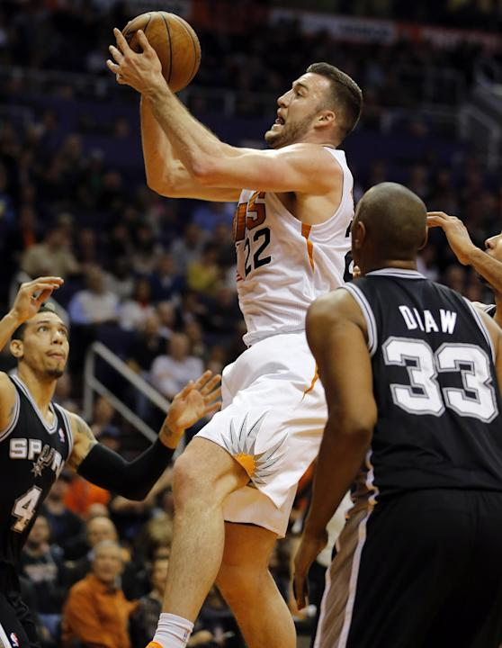 Phoenix Suns' Miles Plumlee (22) drives past San Antonio Spurs' Boris Diaw (33), of France, during the second half of an NBA basketball game, Wednesday, Dec. 18, 2013, in Phoenix. The Spurs wo