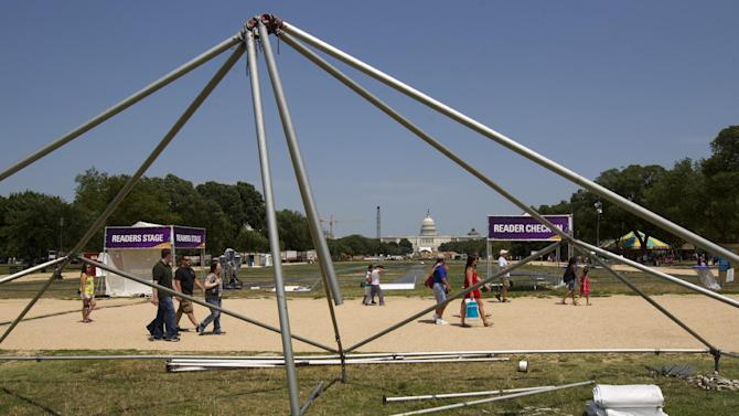 Visitors walk past the frame of a damaged tent at the National Mall in Washington Saturday, June 30, 2012 after a powerful storm swept across the area. Violent storms swept across the eastern U.S., killing at least nine people and knocking out power to hundreds of thousands on a day that temperatures across the region are expected to reach triple-digits.  Officials said about 500,000 people were without power in West Virginia.    (AP Photo/Manuel Balce Ceneta)