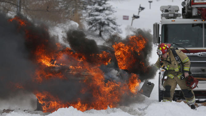 A Lawrence Firefighter places wheel blocks as he prepares to extinguish a vehicle fire in Lawrence, Kan., Thursday, Feb. 21, 2013. The car caught on fire trying to make it up a snow covered hill on Lawrence Avenue. (AP Photo/Orlin Wagner)