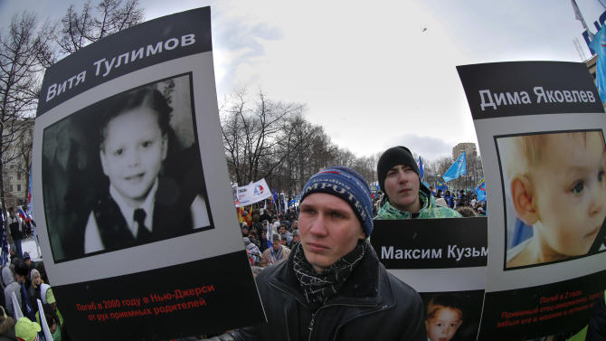 """Demonstrators hold portraits of adopted Russian children who died in U.S., during a massive rally in Moscow, Saturday, March 2, 2013. Russia voiced strong skepticism Saturday about the U.S. autopsy on Max Shatto, a 3-year-old adopted Russian boy in Texas and demanded further investigation as thousands rallied in Moscow to support the Kremlin ban on U.S. adoptions of Russian children. The poster at left reads: """"Vitya Tulimov died in 2000 in New Jersey at the hands of adoptive parents."""" A poster at right reads """"Dima Yakovlev."""" (AP Photo/Alexander Zemlianichenko)"""