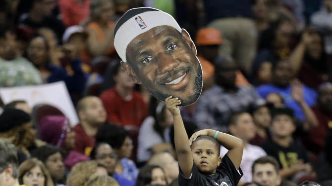 A young Cleveland Cavaliers fan holds up a cutout of LeBron James during an NBA scrimmage basketball game Wednesday, Oct. 1, 2014, in Cleveland. (AP Photo/Tony Dejak)