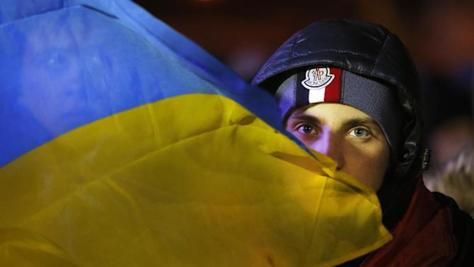 A Ukrainian attends a rally at the central Independence square in Kiev, Ukraine, on Monday, Dec. 2, 2013. Thousands of protesters besieged government buildings in Ukraine's capital on Monday to demand the ouster of the prime minister and his Cabinet, as anger at the president's decision to ditch a deal for closer ties with the European Union gripped other parts of the country and threatened his rule. (AP Photo/Sergei Grits)