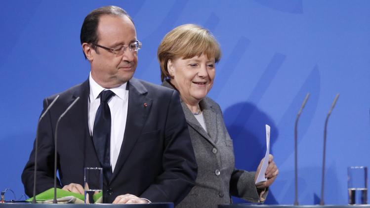 German Chancellor Angela Merkel, right, and  France's President Francois Hollande arrive for a joint statement before their meeting with European Commission President Jose Manuel Barroso at the chancellery in Berlin, Monday, March 18, 2013.  (AP Photo/Markus Schreiber)