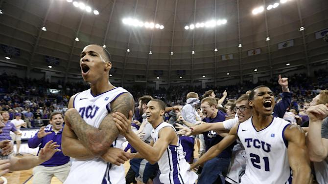 TCU forward Garlon Green, left, and guards Clyde Smith, and Nate Butler Lind (21) celebrate with the fans on the court after an NCAA college basketball game against Kansas on Wednesday, Feb. 6, 2013, in Fort Worth, Texas. TCU won 62-55. (AP Photo/Sharon Ellman)