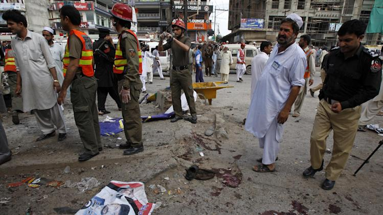 Volunteers and security personnel visit the site of a blast in Peshawar, Pakistan on Monday, April 29, 2013. A suicide bomber targeting policemen killed at least 6 people in northwestern Pakistan on Monday in the latest attack ahead of next month's parliamentary election, police said. (AP Photo/Mohammad Sajjad)