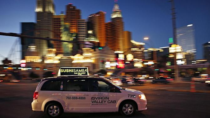 In this Feb. 9, 2016, photo, a taxi drives along Las Vegas Boulevard in Las Vegas. The advent of Uber and Lyft in Nevada last fall has thrown the powerful Las Vegas taxi industry and its regulators into upheaval, as the taxi industry's $3-per-ride credit card processing fee and lack of an online review system look suddenly out of date. (AP Photo/John Locher)