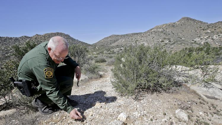 "In this Monday, March 25, 2013 photo, Border Patrol agent Richard Gordon, a 23-year veteran of the agency, examines color changes in the soil which tell him volumes about human traffic where illegal immigrants enter the United States in the Boulevard area east of San Diego  in Boulevard, Calif. For the past 16 years, Gordon has been one of the top ""sign-cutters"" or trackers in the Border Patrol. (AP Photo/Lenny Ignelzi)"