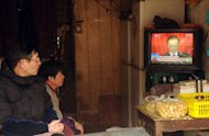 People in Shanghai watch a television set showing Chinese Premier Wen Jiabao speaking during the opening session of the National People's Congress, on March 5, 2013. Chinese inflation hit a 10-month high in February while growth in industrial production and retail sales slowed, official data showed, complicating policymakers' efforts to boost recovery