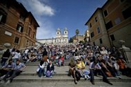 Tourists sit on the Spanish steps in downtown Rome in April 2012. Rising numbers of German and Austrian tourists, as well as visitors from outside Europe, are offsetting a decline in people coming to Italy from other European nations